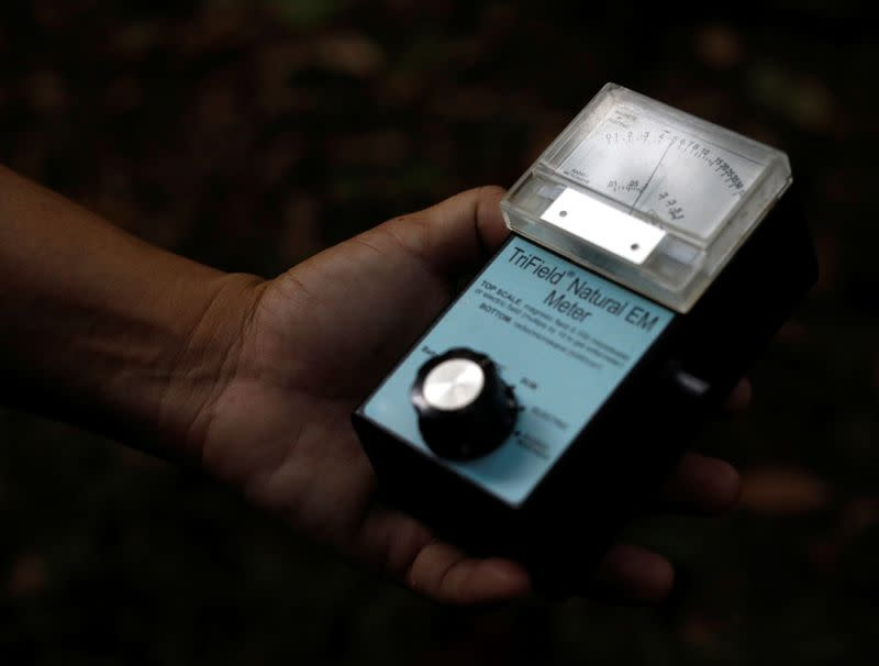 """Paranormal investigator Charles Goh shows a gadget that he uses to """"track"""" paranormal activities in Singapore"""