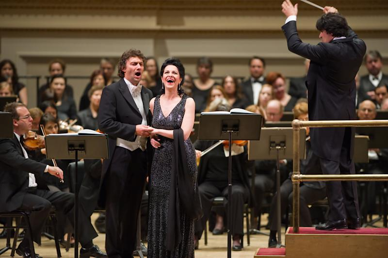 """In this  Nov. 8, 2011 photo provided by Carnegie Hall, Jonas Kaufmann, standing left, and Angela Gheorghiu sing with Alberto Veronesi, right, conducting The Opera Orchestra of New York during a concert performance of """"Adriana Leouvreur"""" at Carnegie Hall in New York. (AP Photo/Carnegie Hall, Stephanie Berger) MANDATORY CREDIT"""