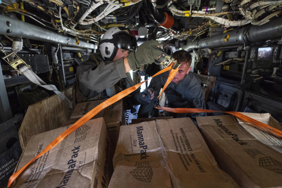"""U.S. Marine Corps Cpl. Thalles Souza, left, and Lance Cpl. Brandon Oldham, unload food from a VM-22 Osprey at Jeremie Airport, Saturday, Aug. 28, 2021, in Jeremie, Haiti. The VMM-266, """"Fighting Griffins,"""" from Marine Corps Air Station New River, from Jacksonville, N.C., are flying in support of Joint Task Force Haiti after a 7.2 magnitude earthquake on Aug. 22, caused heavy damage to the country. (AP Photo/Alex Brandon)"""
