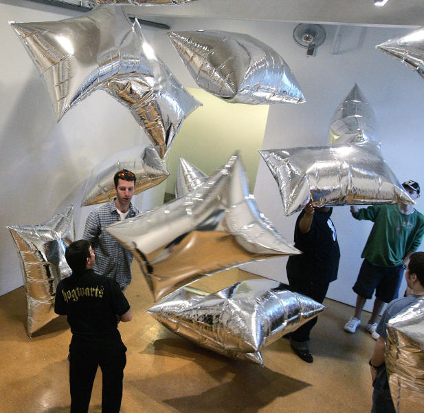 """FILE - In this March 27, 2007, file photo, a group of students play with the reflective mylar pillows floating in the """"Silver Clouds"""" installation room at the Andy Warhol Museum in Pittsburgh. (AP Photo/Keith Srakocic, File)"""