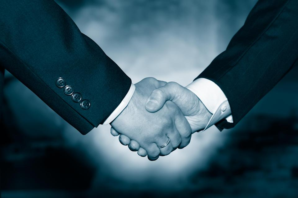 Two businessmen in suits shaking hands as if in agreement.