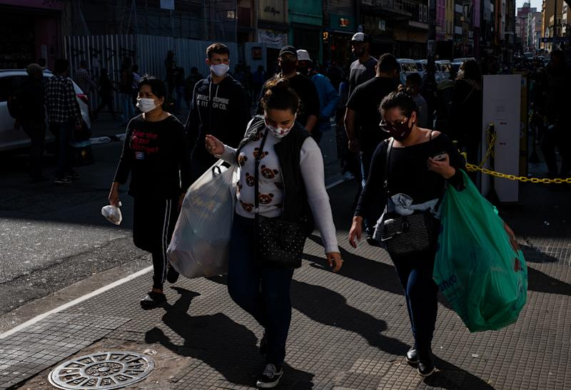 SAO PAULO, BRAZIL - JULY 16: People wearing face masks walk in 25 de Marco, a popular shopping street amidst the coronavirus (COVID-19) pandemic on July 16, 2020 in Sao Paulo, Brazil. Brazil is reaching two million confirmed cases of coronavirus (COVID-19). The country is second only to the United States in number of cases and deaths. According to the Brazilian Health Ministry, Brazil has over 75.000 deaths. (Photo by Alexandre Schneider/Getty Images)