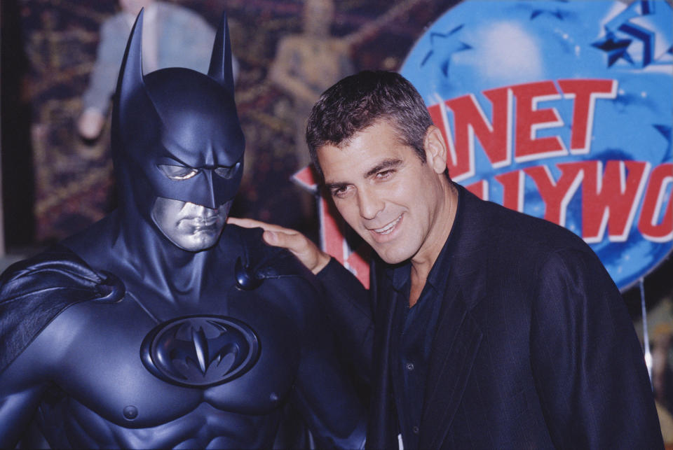 American actor George Clooney poses with a model of Batman during a photocall for his latest film 'Batman and Robin' at Planet Hollywood, London, UK, 23rd June 1997. (Photo by Colin Davey/Getty Images)