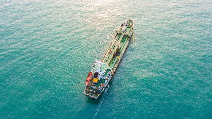An oil tanker sails in blue-green waters.