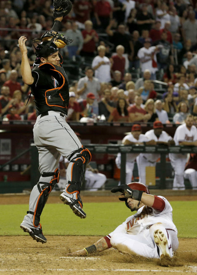 Arizona Diamondbacks' Gerardo Parra, right, scores a run as Miami Marlins' Jeff Mathis jumps to make a catch on the throw to home plate during the fifth inning of a baseball game on Monday, June 17, 2013, in Phoenix. (AP Photo/Ross D. Franklin)