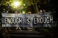 "Protestors hold a banner reading ""enough is enough"" during a rally after the death of Walter Wallace Jr., a Black man who was shot by police in Philadelphia"