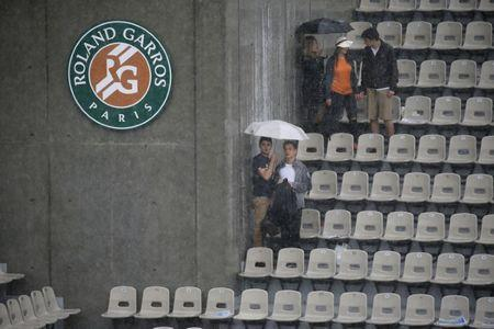 Tennis - French Open - Roland Garros - Venus Williams of the U.S. v Alize Cornet of France - Paris, France - 28/05/16. People hold umbrellas to protect themselves from the rain.   REUTERS/Gonzalo Fuentes