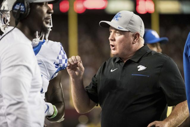 Kentucky head coach Mark Stoops talks with a player on the sideline during the first half of an NCAA college football game against South Carolina Saturday, Sept. 28, 2019, in Columbia, S.C. (AP Photo/Sean Rayford)