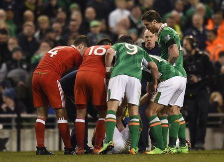 Players surround Republic of Ireland's Seamus Coleman as he lies injured