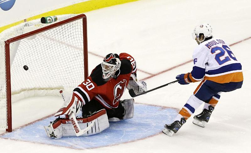 New York Islanders left wing Matt Moulson (26) scores on New Jersey Devils goalie Martin Brodeur (30) during the shootout in an NHL hockey game Friday, Oct. 4, 2013, in Newark, N.J. The Islanders won 4-3 (AP Photo/Julio Cortez)