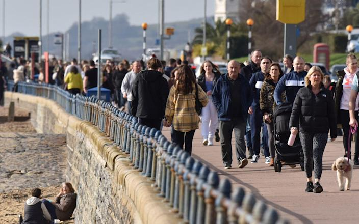 SOUTHEND, ENGLAND - FEBRUARY 21: People walk beside the beach on a warm sunny day as the weather warms for the week ahead on February 21, 2021 in Southend, England. Temperatures are predicted to rise to 18C for parts of the UK this week as a hot air plume is set to arrive from the Canary islands. After a surge of covid-19 cases, fueled partly by a more infectious variant of the virus, the British government had reimposed nationwide lockdown measures across England. A review was held on February 15 and despite deaths and infections falling, lockdown will continue. - John Keeble/Getty Images