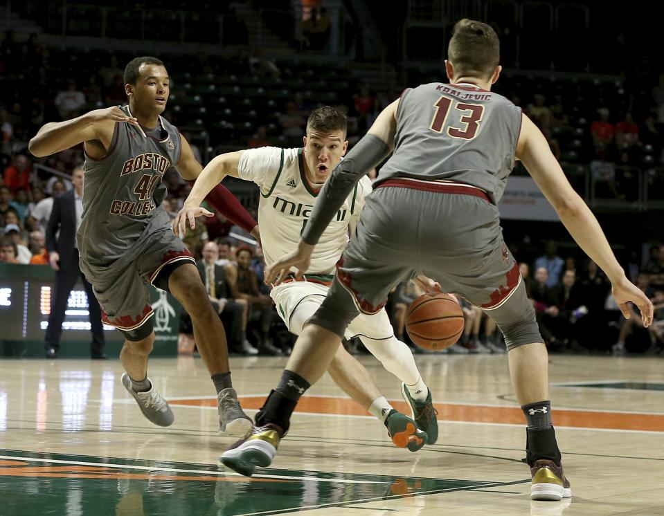 Miami guard Dejan Vasiljevic, center, drives to the basket against Boston College forwards Steffon Mitchell, left, and Luka Kraljevic, right, in the second half of an NCAA college basketball game in Coral Gables, Fla., Saturday, Feb. 24, 2018. (Pedro Portal/Miami Herald via AP)
