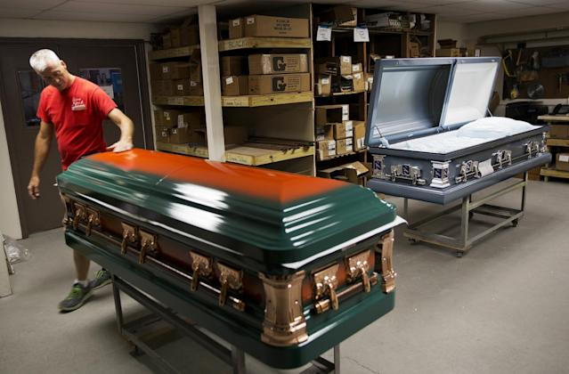 "<p>Kelly Greenwood, co-owner of Cardinal Casket Company, inspects a casket painted in the colors of the University of Miami for a victim of the Pulse nightclub shooting who was also a fan of the university in Orlando. ""It hits you, it hits everyone here,"" said Greenwood, who lost a friend in the shooting. ""I feel proud knowing that I made something for my friend's mother that will be with them the last time their family sees him."" The locally owned company has so far received 23 orders for caskets before the funerals for the victims. <em>(Photo: David Goldman/AP)</em> </p>"