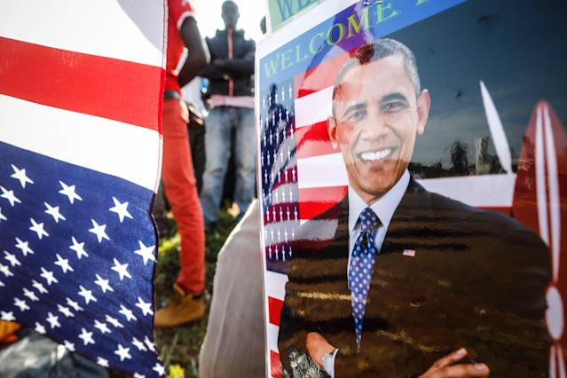 <p>A supporter of former US president Barack Obama wears a laminated badge featuring Obama, as he stands with others on the street and waits for Obama's arrival prior to an opening ceremony of the Sauti Kuu Sports, Vocational and Training Centre in his ancestral home Kogelo, some 400km west of the capital Nairobi, Kenya on 16, July 2018. (Photo: Dai Kurokawa/EPA-EFE/REX/Shutterstock) </p>