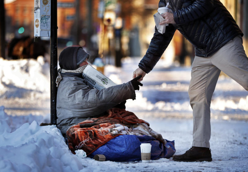 A homeless man sitting outside a coffee shop accepts cash from a customer on a bitter cold morning, Thursday, Jan. 31, 2019, in Portland, Maine, The polar vortex that's bringing misery to the upper Midwest is making an appearance in northern New England, where some places will struggle to reach the single digits. (AP Photo/Robert F. Bukaty)