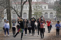 """'Curly Shirley' Catton, back to camera, left of center, leads her students in her High on Life"""" fitness class in front of the Audubon Boathouse, Thursday, Jan. 14, 2021, at Brooklyn's Prospect Park in New York. """"I just love the park because there's always a new route to take,"""" Catton said. (AP Photo/Kathy Willens)"""