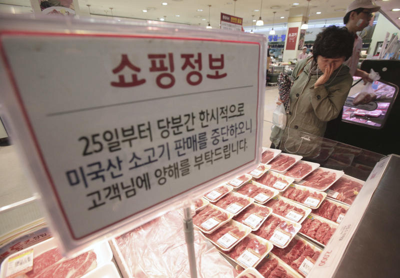 """A South Korean woman watches Australian beef on the shelves at a Lotte Mart store in Seoul, South Korea, Wednesday, April 25, 2012. Two major South Korean retailers, including Lotte Mart,  suspended sales of U.S. beef Wednesday following the discovery of mad cow disease in a U.S. dairy cow. Reaction elsewhere in Asia was muted with Japan saying there's no reason to restrict imports. The letters on a card read """" Starting from the 25th, we will temporarily stop the sales of the US beef. Thank you for your understanding"""". (AP Photo/Ahn Young-joon)"""