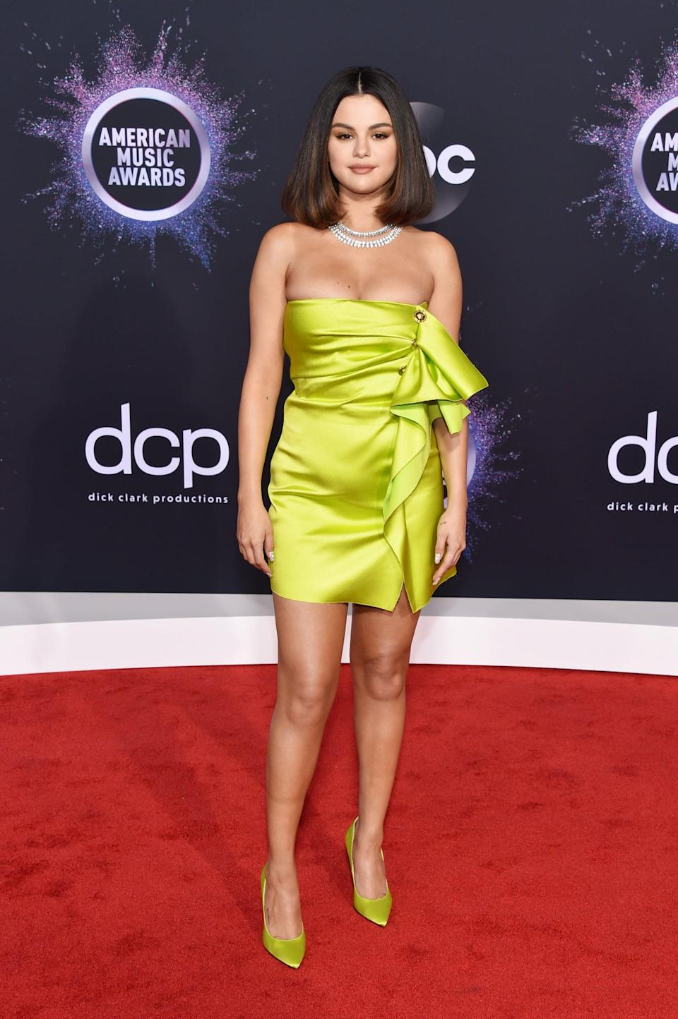 """<p>Selena wore a <a href=""""https://www.popsugar.com/fashion/selena-gomez-versace-dress-at-the-american-music-awards-2019-46941093"""" class=""""link rapid-noclick-resp"""" rel=""""nofollow noopener"""" target=""""_blank"""" data-ylk=""""slk:Versace minidress"""">Versace minidress</a> with Roberto Coin jewels and matching Versace pumps to the 2019 American Music Awards in LA.</p>"""