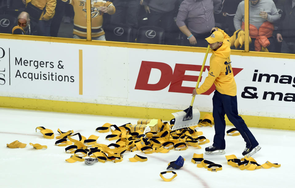 Visors and caps are cleared from the ice after Nashville Predators' Filip Forsberg, of Sweden, had a hat trick against the Columbus Blue Jackets during the third period of an NHL hockey game Saturday, April 7, 2018, in Nashville, Tenn. (AP Photo/Mark Zaleski)
