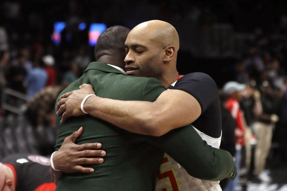 FILE - In this March 11, 2020, file photo, Atlanta Hawks guard Vince Carter, right, hugs former Hawk Dominique Wilkins as he leaves the court following an NBA basketball game against the New York Knicks in Atlanta. When the NBA announced the night of March 11 that it would be halting play because of the pandemic, word filtered through the arena and all the way down to the bench of the shocking developments. The fans began chanting for Carter to enter a game for the Hawks in the closing seconds. Carter had already announced it would be the final season of his brilliant 23-year career, longer than anyone else has played in the NBA. The fans sensed that the season might be over. The Hawks sent him back to the court. The Knicks respectfully backed away to give him an open look at a 3-pointer. (AP Photo/John Bazemore, File)