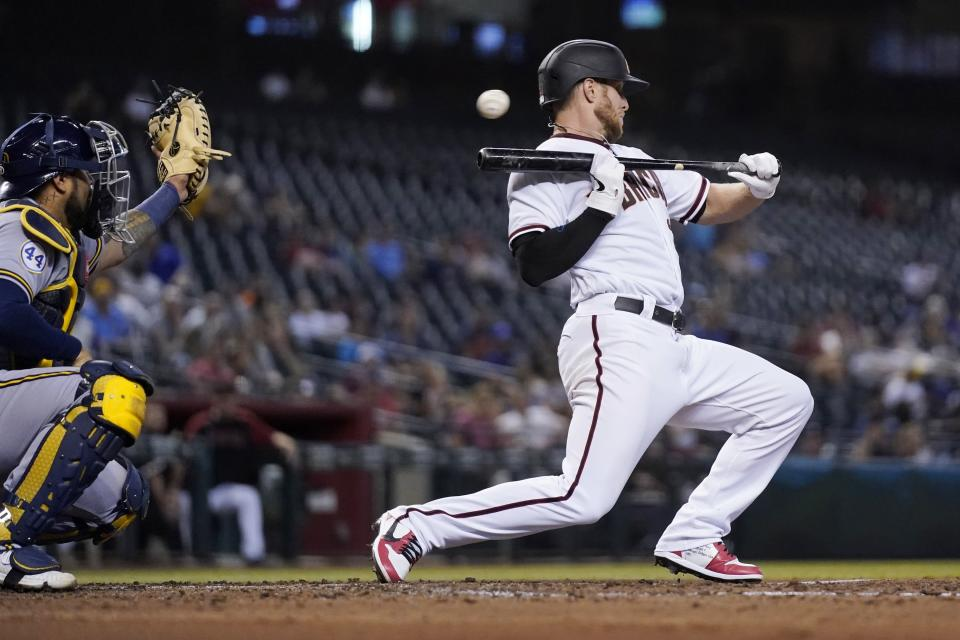Arizona Diamondbacks' Merrill Kelly backs away from a bunt attempt as Milwaukee Brewers catcher Omar Narvaez, left, reaches out for the inside pitch during the second inning of a baseball game Monday, June 21, 2021, in Phoenix. (AP Photo/Ross D. Franklin)