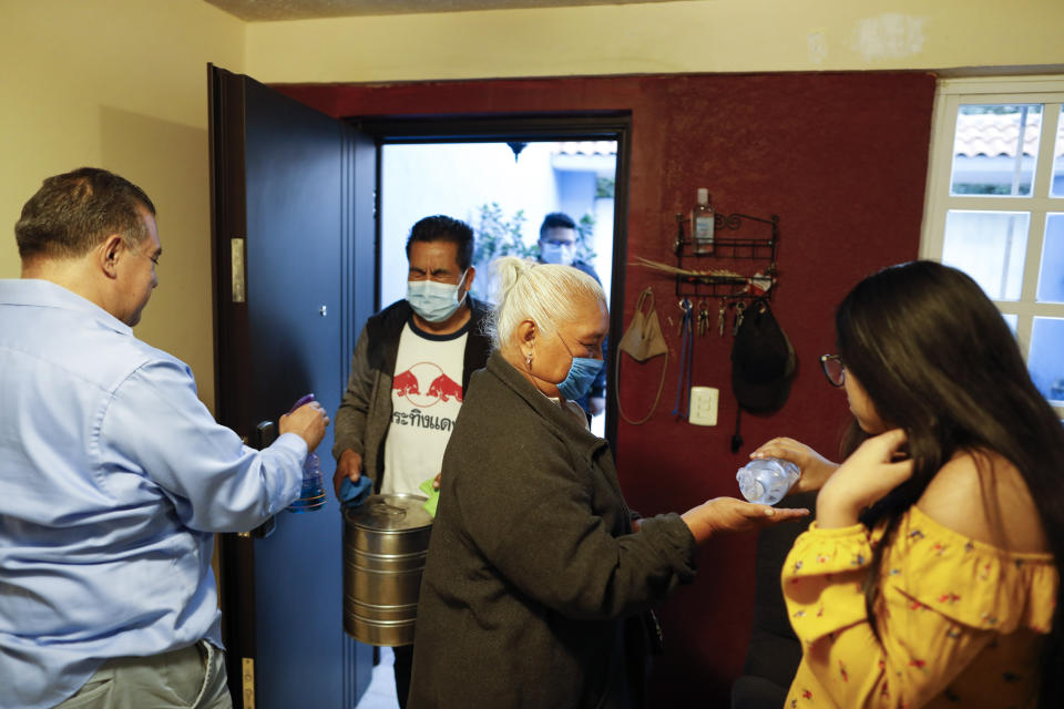 Ximena Canejo Hernandez, right, gives antibacterial gel to her grandmother Eloisa Santos Castillo, as Ximena's father, Alejandro Canejo Lopezk sprays disinfectant onto his in-laws, arriving for a simple event at home to mark Ximena's 15th birthday, in Tlalnepantla, just outside Mexico City, Monday, July 13, 2020. Ximena's family, wanting to give her a traditional quinceanera, had booked a church and event hall for July 18th long before the coronavirus pandemic hit, but the celebration had to be postponed until late November. The family had been following stay at home guidance, but with Mexico City's opening beginning in recent weeks, Ximena's grandmother decided to travel up from Oaxaca for her birthday, the first visit to her daughters and grandchildren in more than four months. (AP Photo/Rebecca Blackwell)