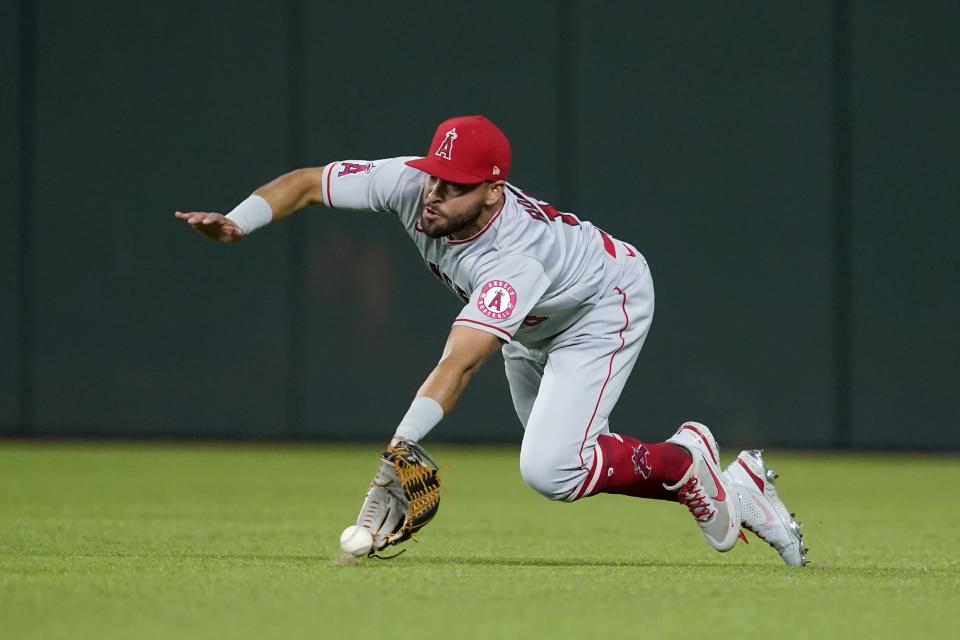 Los Angeles Angels right fielder Jose Rojas makes a diving attempt to reach a single hit by Texas Rangers' Jonah Heim in the sixth inning of a baseball game in Arlington, Texas, Tuesday, Sept. 28, 2021. (AP Photo/Tony Gutierrez)