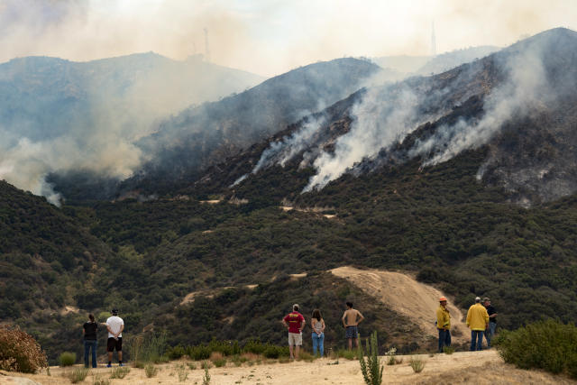 <p>People watch the La Tuna Canyon fire in Los Angeles, Calif. on Sept. 2, 2017. (Photo: Ronen Tivony/NurPhoto via Getty Images) </p>