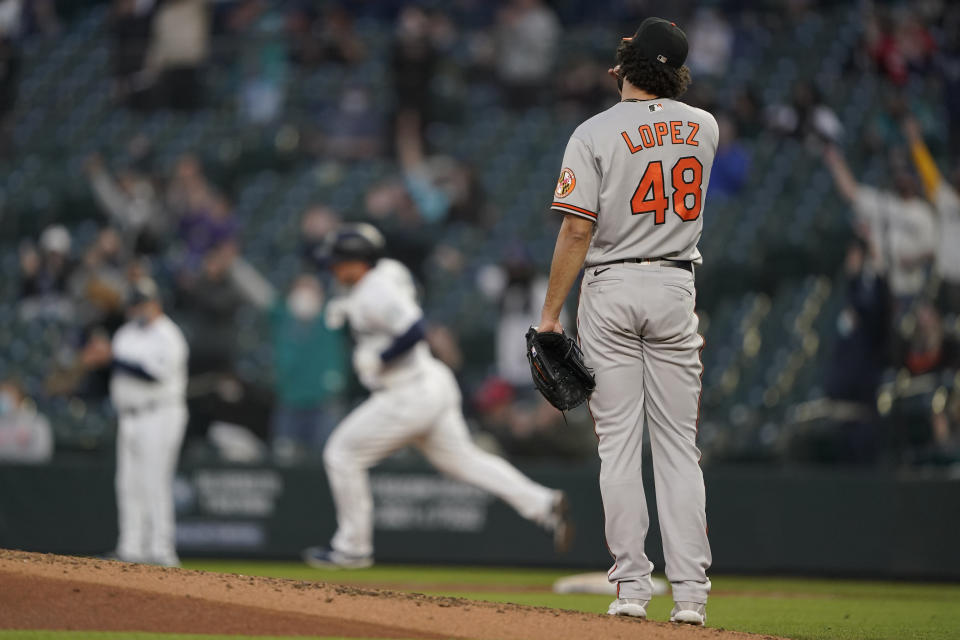 Baltimore Orioles starting pitcher Jorge Lopez watches as Seattle Mariners' Kyle Seager rounds the bases after hitting a solo home run during the fourth inning of a baseball game, Tuesday, May 4, 2021, in Seattle. (AP Photo/Ted S. Warren)