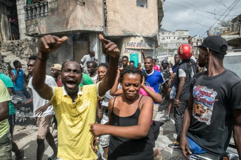 The crowd reacts at the Jalousie township as armed men, accused of being involved in the assassination of President Jovenel Moise, are being arrested in Port au Prince on July 8, 2021