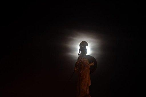 The full moon rises behind a statue of the ancient goddess Athena in Athens