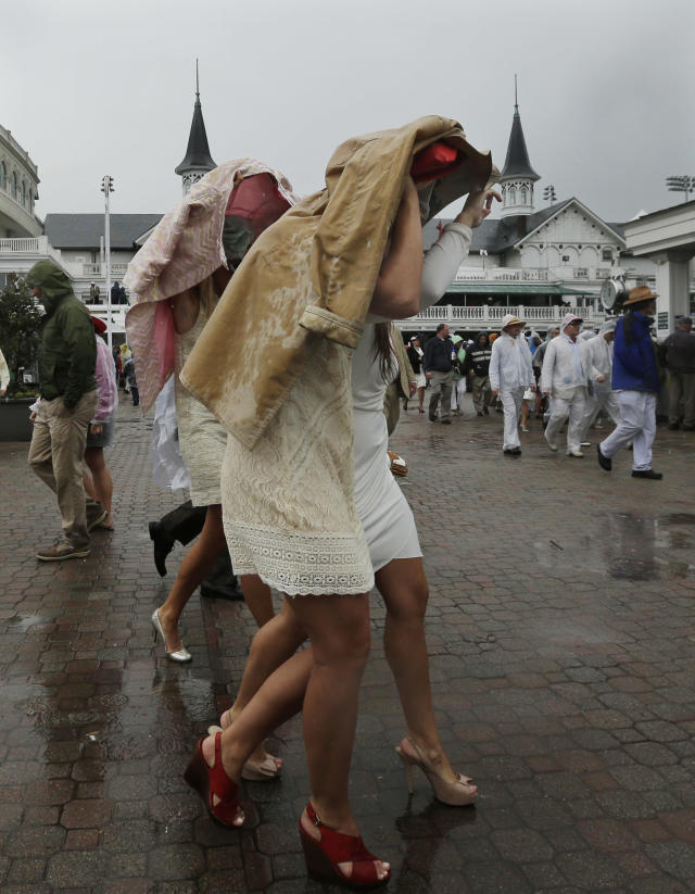 Race goers take cover from rain under their jackets before the 139th Kentucky Derby at Churchill Downs Saturday, May 4, 2013, in Louisville, Ky. (AP Photo/Charlie Riedel)