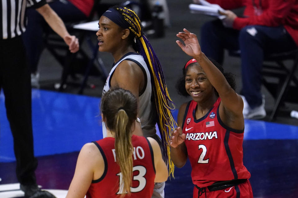 Arizona guard Aari McDonald (2) celebrates with teammate guard Helena Pueyo (13) in front of Connecticut forward Aaliyah Edwards after getting fouled during the second half of a women's Final Four NCAA college basketball tournament semifinal game Friday, April 2, 2021, at the Alamodome in San Antonio. (AP Photo/Eric Gay)
