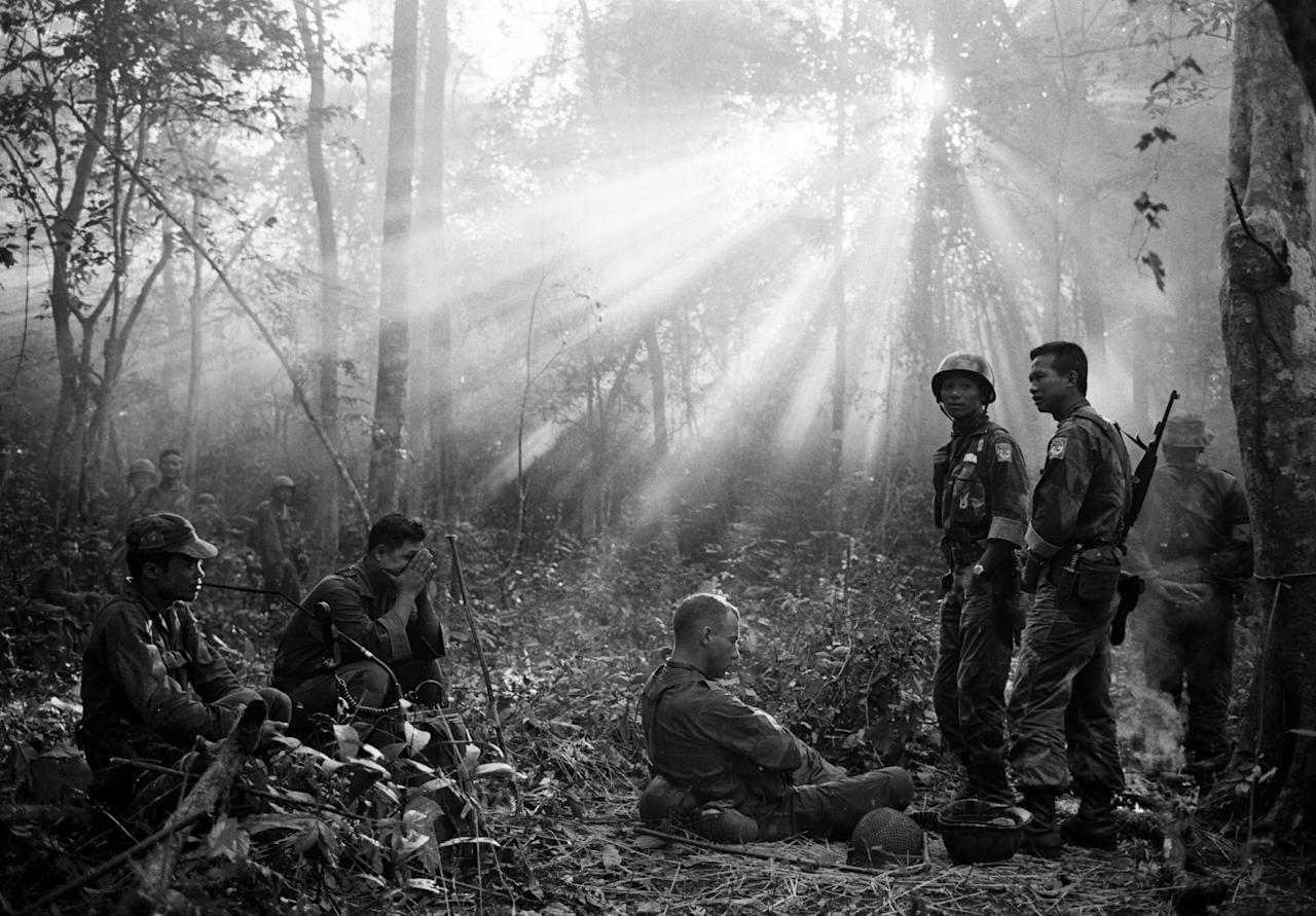 FILE - In this January 1965 file photo taken by Associated Press photographer Horst Faas, the sun breaks through dense jungle foliage around the embattled town of Binh Gia, 40 miles east of Saigon, as South Vietnamese troops, joined by U.S. advisers, rest after a cold, damp and tense night of waiting in an ambush position for a Viet Cong attack that didn't come. Faas, a prize-winning combat photographer who carved out new standards for covering war with a camera and became one of the world's legendary photojournalists in nearly half a century with The Associated Press, died Thursday May 10, 2012. He was 79. (AP Photo/Horst Faas, File)