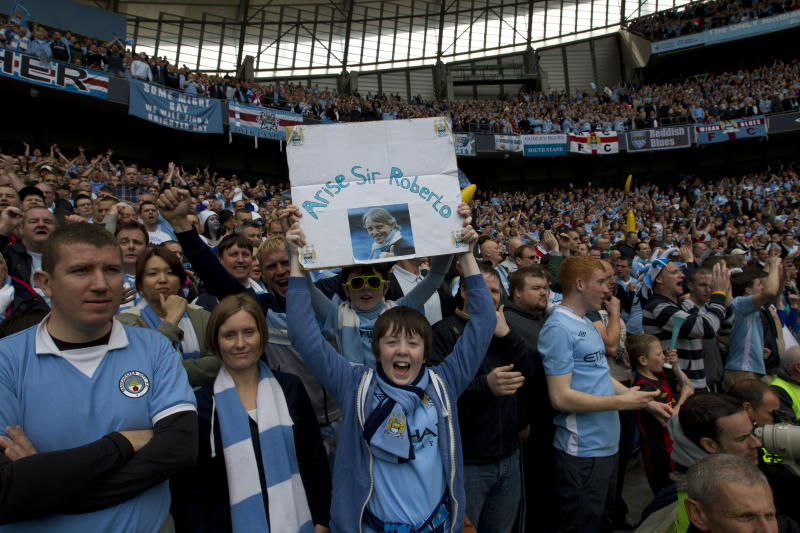 A Manchester City holds up a banner praising manager Roberto Mancini before the team's English Premier League soccer match against Queens Park Rangers at The Etihad Stadium, Manchester, England, Sunday May 13, 2012. Manchester City won the game and in so doing the English Premier League for the first time in 44 years. (AP Photo/Jon Super)