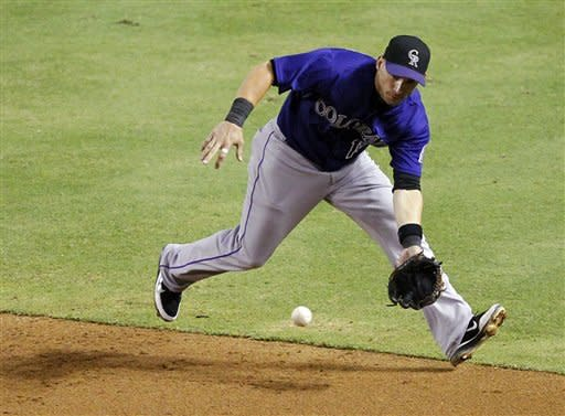 Colorado Rockies' Marco Scutaro fields a ground out hit by Arizona Diamondbacks' Justin Upton during the fifth inning of a baseball game, Monday, July 23, 2012, in Phoenix. (AP Photo/Matt York)