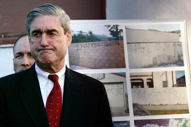 <p>FBI Director Robert Mueller grimaces while listening to Los Angeles Mayor Antonio Villaraigosa speaking of the death of Cheryl Green, during a news conference announcing anti-gang measures, Thursday Jan. 18, 2007 in Wilmington, Calif. Authorities announced Thursday an offensive against the Hispanic gang allegedly behind the racially charged shooting death of Cheryl Greenl, the first part of what they said will be a major crackdown on street gangs this year. In the background photos of the 204th Street gang graffiti. (Photo: Damian Dovarganes/AP) </p>