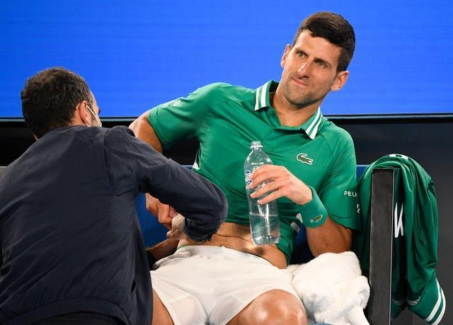 Novak Djokovic receives treatment during his victory over Taylor Fritz