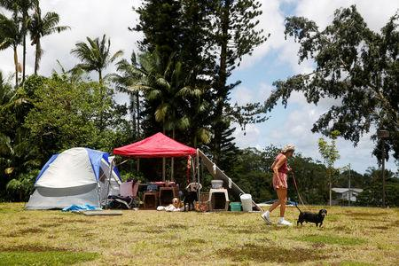 Pauline McLaren, 77, of Kapoho, walks one of her five dogs near her tents at a Red Cross evacuation center in Pahoa during ongoing eruptions of the Kilauea Volcano in Hawaii, U.S., May 15, 2018.  REUTERS/Terray Sylvester