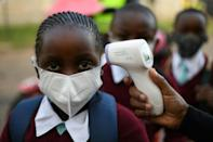 Kenyan students from Our Lady of Mercy Primary School Nairobi South have their temperature measured as they resume in-class learning after a nine-month disruption caused by the pandemic
