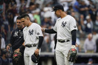 New York Yankees' Aaron Judge, right, checks on Gio Urshela, center, after he was hurt running into the Tampa Bay Rays dugout chasing a ball hit by Austin Meadows for an out during the sixth inning of a baseball game Sunday, Oct. 3, 2021, in New York. (AP Photo/Frank Franklin II)