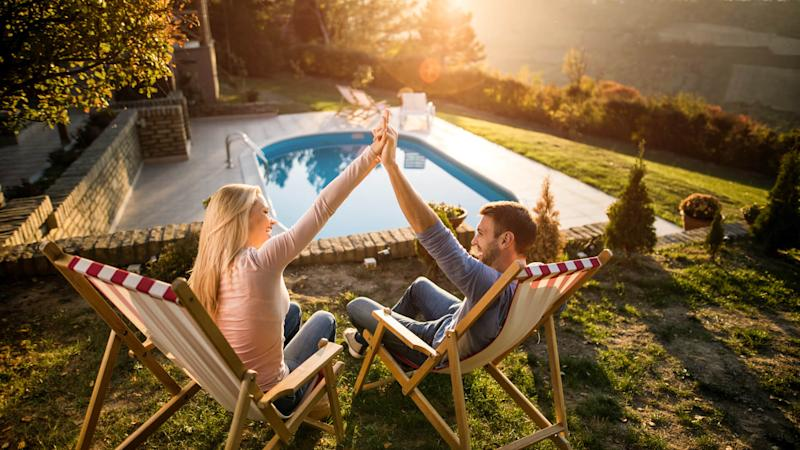 Young happy couple relaxing in deck chairs at their back yard and holding their arms together.