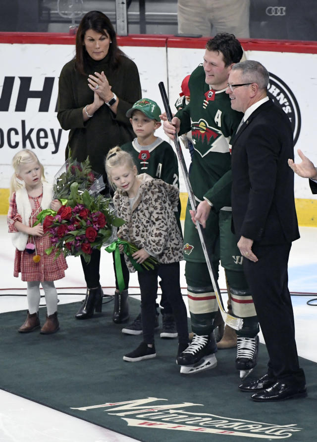 Minnesota Wild general manager Paul Fenton presents defenseman Ryan Suter with a silver stick after Suter played in his 1,000th NHL hockey game earlier in the week, while his children and mother, Diane, watch before a hockey game, Saturday, Oct. 27, 2018, in St. Paul, Minn. (AP Photo/Hannah Foslien)