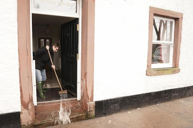 A resident sweeps floodwater from a property in Appleby-in-Westmorland, Cumbria. (PA)