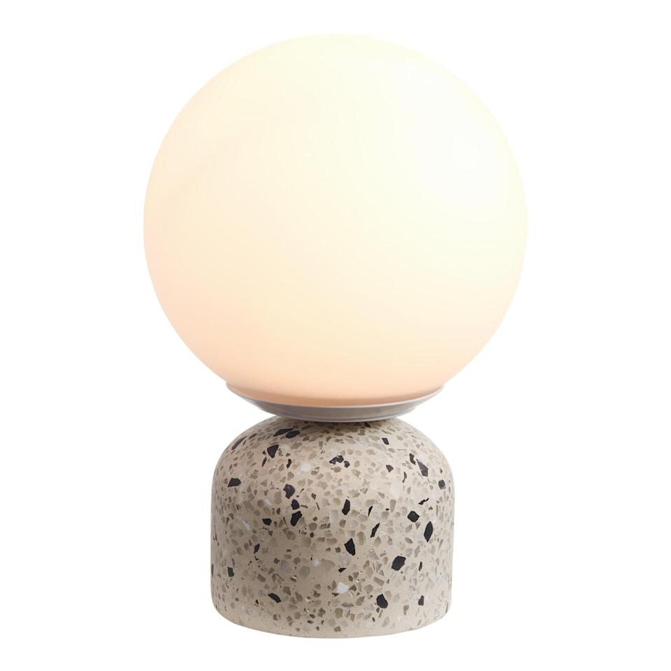 """Terrazzo is a trend that's been <a href=""""https://www.thecut.com/2020/03/will-the-millennial-aesthetic-ever-end.html"""" target=""""_blank"""" rel=""""noopener noreferrer"""">especially popular with millennials</a>. But this lamp doesn't look too trendy, and the neutral colors won't clash with your planters. It features aspeckled base andfrosted-glass globe shade. You should get a <a href=""""https://amzn.to/3iyHhsl"""" target=""""_blank"""" rel=""""noopener noreferrer"""">25-watt light bulb</a>for it. <a href=""""https://fave.co/2ZGXLr8"""" target=""""_blank"""" rel=""""noopener noreferrer"""">Find it for $50 at World Market</a>."""