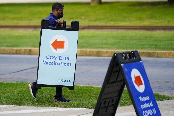 A worker posts placard for a COVID-19 vaccination clinic at the Reading Area Community College in Reading, Pa., Tuesday, Sept. 14, 2021. (AP Photo/Matt Rourke)
