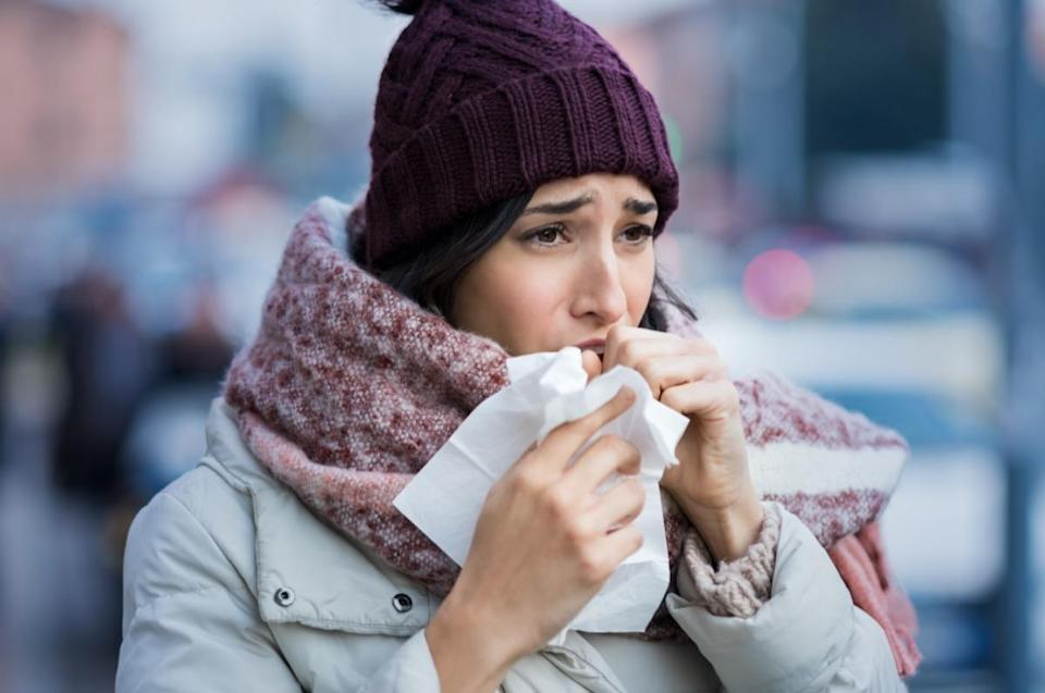 Young woman coughing during winter on street
