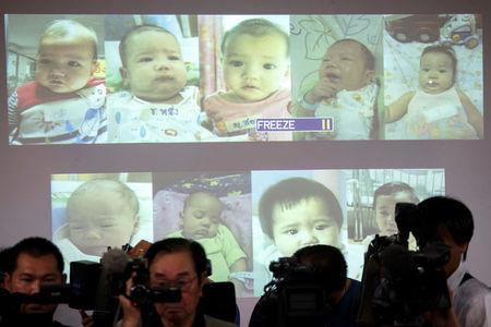 FILE PHOTO: Surrogate babies that Thai police suspect were fathered by a Japanese businessman who has fled from Thailand are shown on a screen during a news conference at the headquarters of the Royal Thai Police in Bangkok