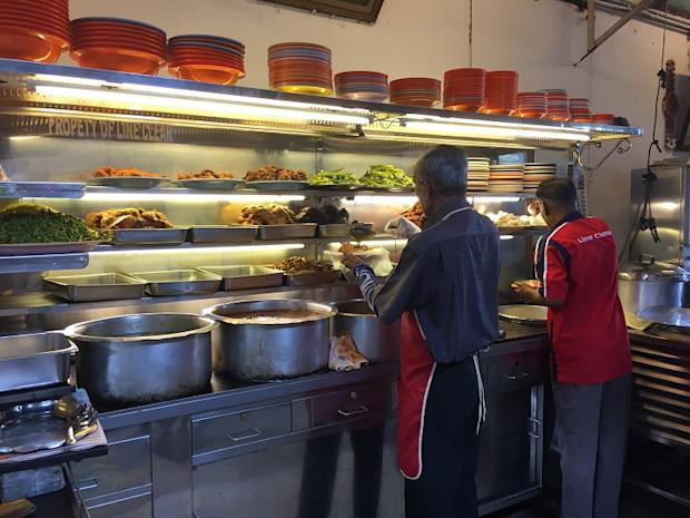Workers setting up the counter with pots of curries and dishes from 8am onwards.