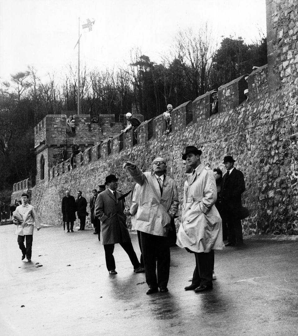 Prince Philip visiting Wales. Rear Admiral D J Hoare the headmaster of the Atlantic College points out features of the South Wales coastline to the Duke of Edinburgh. Behind them battlements of St Donat's Castle, with boys. November 1963. (Photo by Staff/Mirrorpix/Getty Images)